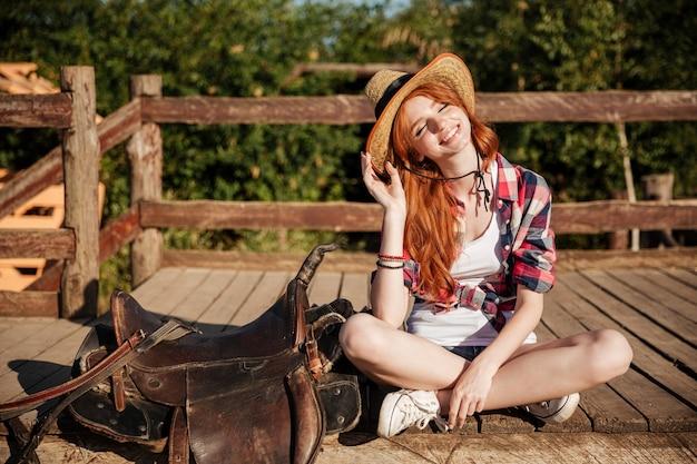 Porträt des lächelnden cowgirls der jungen frau im hut und im karierten hemd