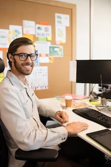 Porträt des lächelnden designers, der am kreativen büro sitzt