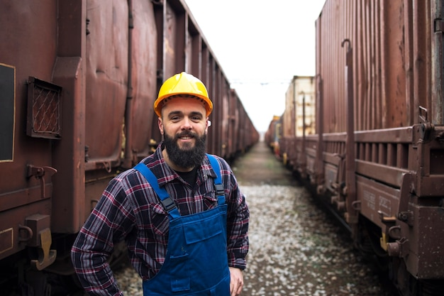 Porträt des lächelnden eisenbahnarbeiters, der zwischen güterzügen steht