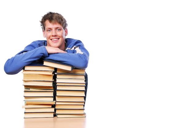 Porträt des lächelnden erwachsenen jungen klugen mannes, der auf dem haufen bücher aufgezeichnet wird
