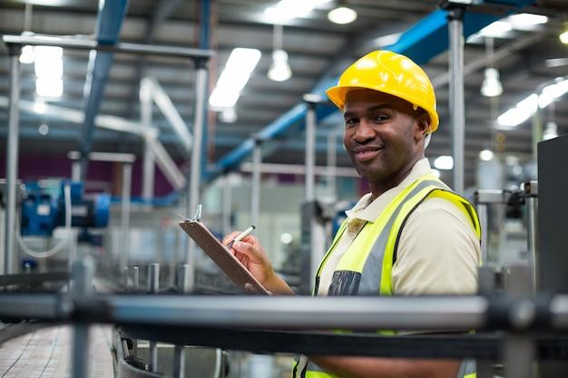 Porträt des lächelnden fabrikarbeiters, der auf zwischenablage in der fabrik schreibt