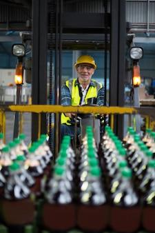 Porträt des lächelnden fabrikarbeiters, der gabelstapler fährt