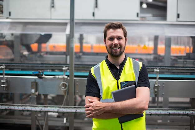 Porträt des lächelnden fabrikarbeiters, der mit einem digitalen tablett steht