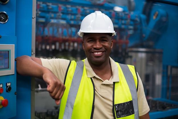 Porträt des lächelnden fabrikarbeiters, der sich auf maschinensteuerschrank stützt