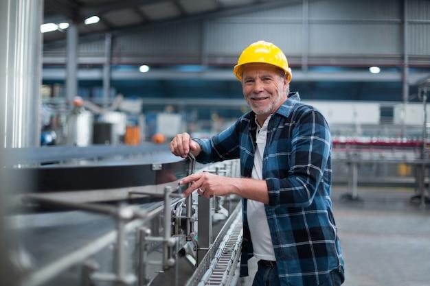 Porträt des lächelnden fabrikarbeiters nahe produktionslinie