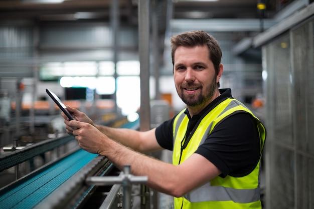 Porträt des lächelnden fabrikarbeiters unter verwendung einer digitalen tablette