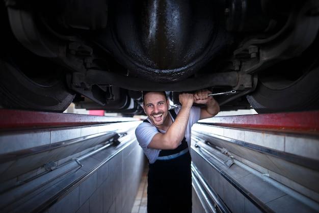 Porträt des lächelnden fahrzeugmechanikers, der schraubenschlüssel hält und unter dem lkw in der fahrzeugreparaturwerkstatt arbeitet