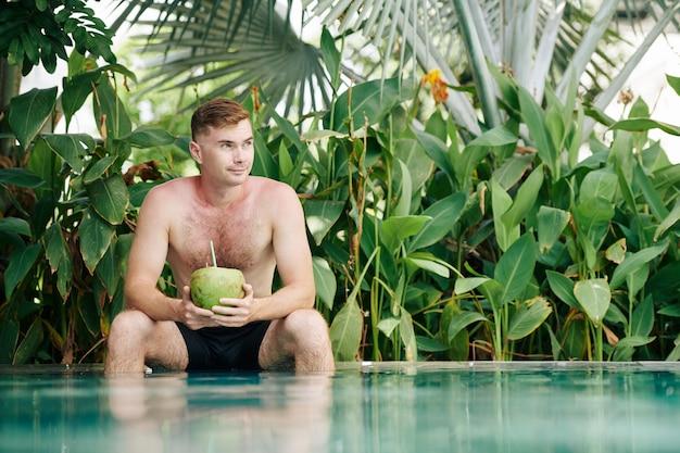 Porträt des lächelnden fot hemdlosen mannes, der am rand des schwimmbades sitzt, kokosnusscocktail trinkt und wegschaut