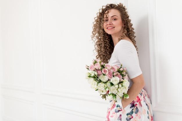 Porträt des lächelnden gelockten blonden mädchens lernte auf der weißen wand und hält einen blumenstrauß von rosen