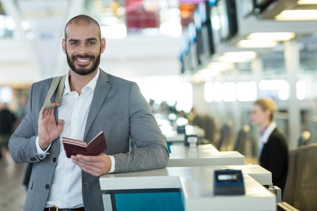 Porträt des lächelnden geschäftsmannes, der am check-in-schalter mit pass und bordkarte steht