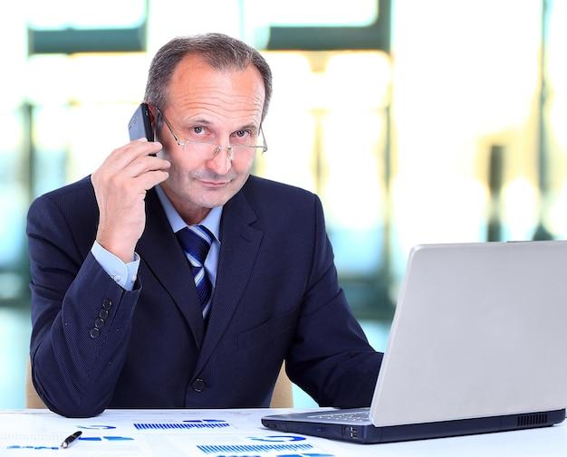 Porträt des lächelnden geschäftsmannes, der auf handy spricht und an einem laptop im büro arbeitet