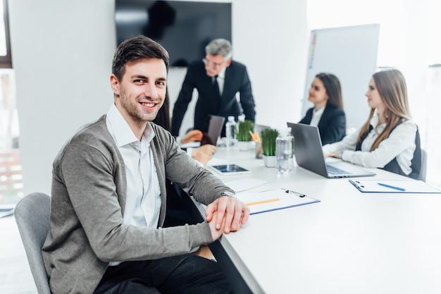 Porträt des lächelnden geschäftsmannes, der im büro arbeitet
