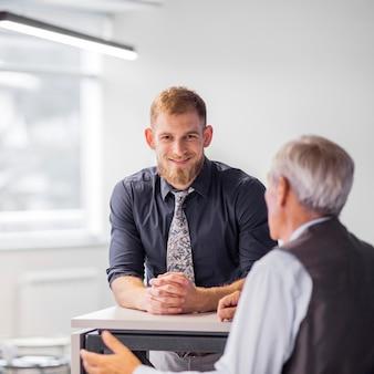 Porträt des lächelnden geschäftsmannes mit seinem kollegen im büro