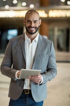 Porträt des lächelnden geschäftsmannes unter verwendung der digitalen tablette im wartebereich