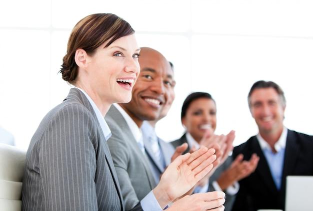Porträt des lächelnden geschäftsteams, das eine darstellung applaudiert