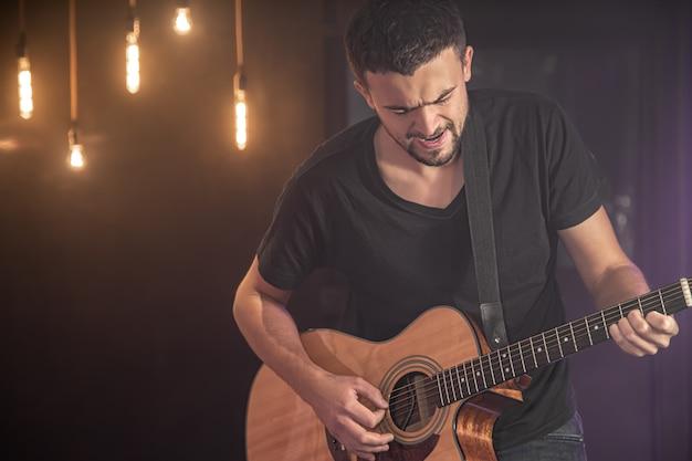 Porträt des lächelnden gitarristen im schwarzen t-shirt, das akustikgitarre auf der dunklen wand des unscharfen studios spielt.