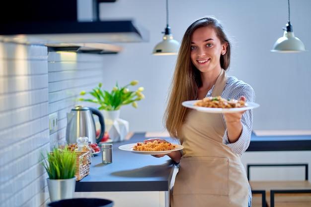 Porträt des lächelnden glücklichen freudigen niedlichen kochenden frauenkochs, der schürze hält, die einen nudelteller für abendessen hält
