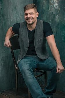Porträt des lächelnden glücklichen mannes, der auf dem hölzernen stuhl auf grauem studio sitzt