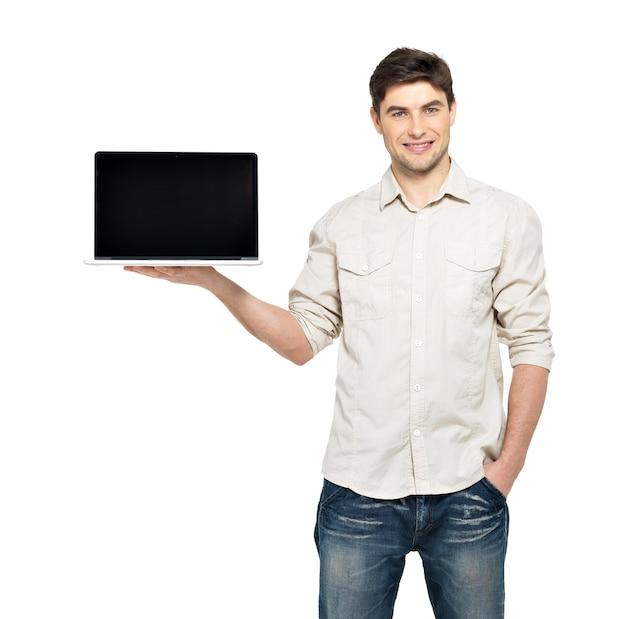 Porträt des lächelnden glücklichen mannes hält laptop auf handfläche mit leerem bildschirm - lokalisiert auf weiß. konzeptkommunikation.