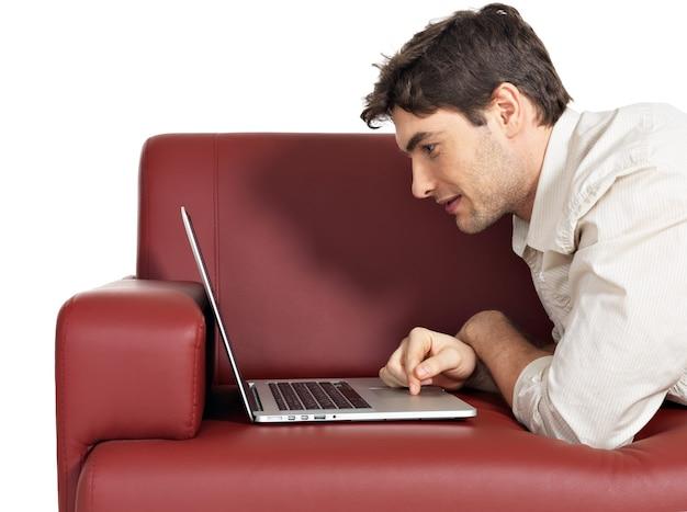 Porträt des lächelnden glücklichen mannes mit laptop auf diwan, lokalisiert auf weiß.