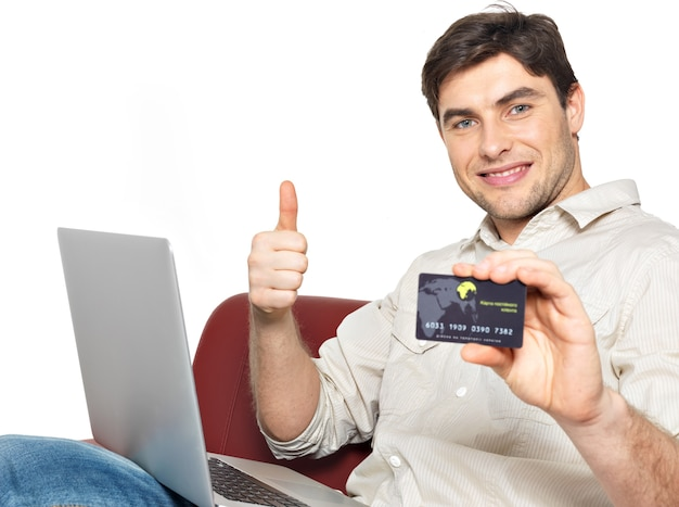 Porträt des lächelnden glücklichen mannes mit laptop gibt die daumen auf und zeigt die kreditkarte, die auf weiß isoliert wird.