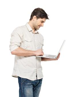 Porträt des lächelnden glücklichen mannes mit laptop in lässig - lokalisiert auf weiß. konzeptkommunikation.