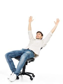 Porträt des lächelnden glücklichen mannes sitzt auf dem stuhl und hob die hände lokalisiert auf weiß.