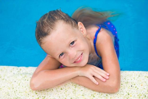 Porträt des lächelnden glücklichen netten mädchens swimmingpool im im freien