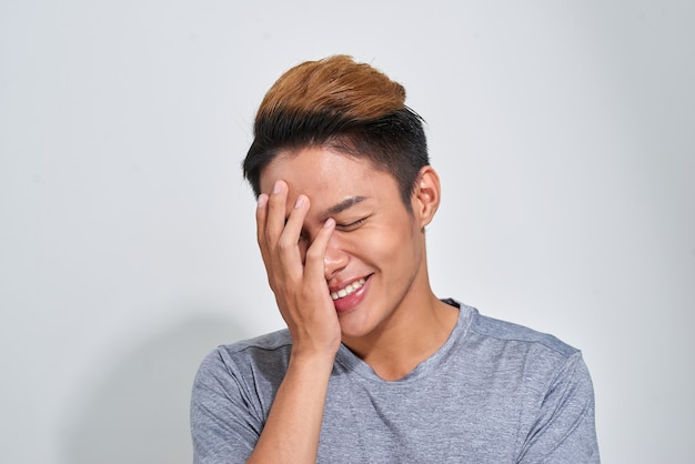 Porträt des lächelnden glücklichen sportmannes, der t-shirt über grauem studiohintergrund trägt