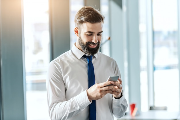Porträt des lächelnden gutaussehenden bärtigen geschäftsmannes in hemd und krawatte unter verwendung des smartphones, während im büro neben fenster stehend.