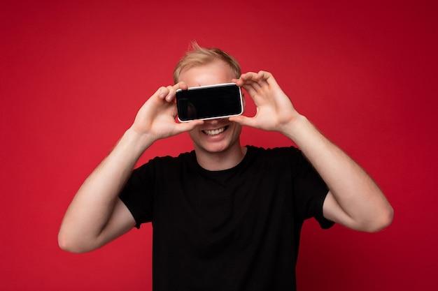 Porträt des lächelnden gutaussehenden blonden jungen mannes, der das schwarze t-shirt trägt, das lokal auf der roten oberfläche steht, die das handy zeigt, das smartphone in der hand mit leerem display für modell zeigt