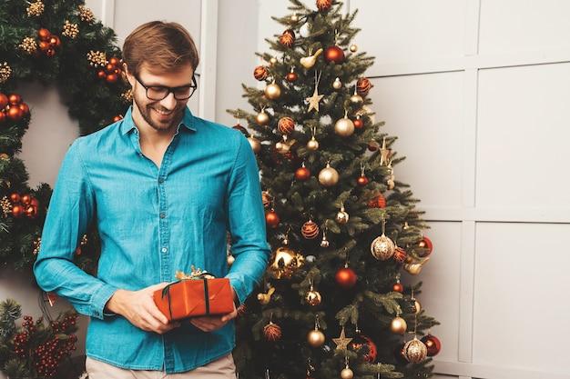 Porträt des lächelnden gutaussehenden mannes, der geschenk hält. sexy bärtiger mann, der nahe weihnachtsbaum mit geschenk aufwirft.