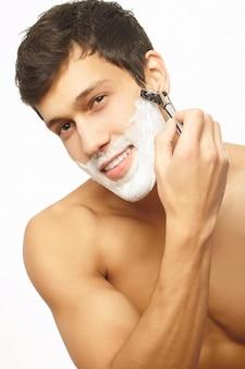 Porträt des lächelnden gutaussehenden mannes, der sich rasiert