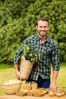 Porträt des lächelnden gutaussehenden mannes organisches gemüse verkaufend