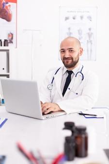 Porträt des lächelnden händchenhaltens des doktors auf laptoptastatur, die kamera im krankenhausbüro mit laborkittel betrachtet. arzt mit notebook am klinikarbeitsplatz, fachwissen, medizin.