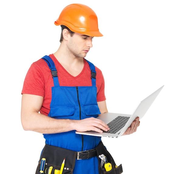 Porträt des lächelnden handwerkers mit laptop lokalisiert auf weiß