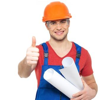 Porträt des lächelnden handwerkers mit werkzeugen und papier, die daumen auf zeichen lokalisiert auf weiß zeigen
