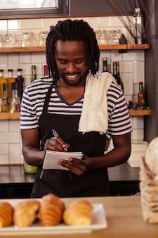 Porträt des lächelnden hipsters, der eine bestellung bei der arbeit nimmt