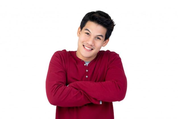 Porträt des lächelnden hübschen asiatischen mannes der junge mit seinen armen gekreuzt