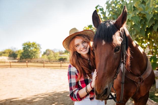 Porträt des lächelnden hübschen cowgirls der jungen frau im hut mit ihrem pferd