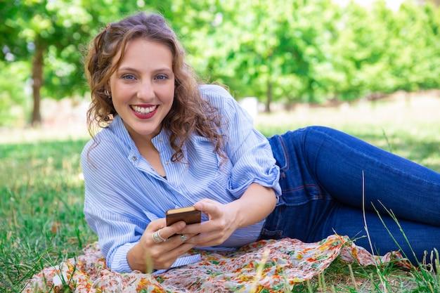 Porträt des lächelnden hübschen mädchens, das mobiles internet verwendet
