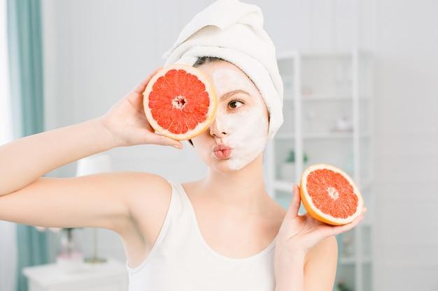 Porträt des lächelnden hübschen mädchens mit weißem handtuch auf kopf, das hälften von grapefruits nahe gesicht schließt ein auge schließt, gesunde perfekte glatte haut, weiße maske auf einer gesichtshälfte, über hellem raum