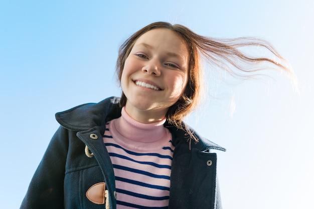 Porträt des lächelnden jugendlich mädchens der junge, blauer himmel des hintergrundes