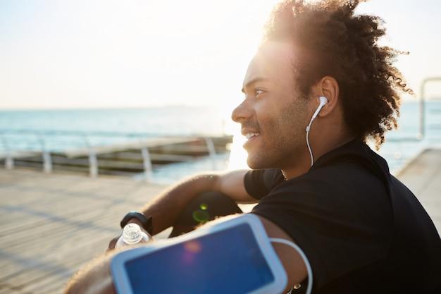Porträt des lächelnden jungen afroamerikanischen sportlers mit kopfhörern auf im schwarzen t-shirt. nach erfolgreichem joggen auf einem holzsteg ruhen. übungen am meer machen