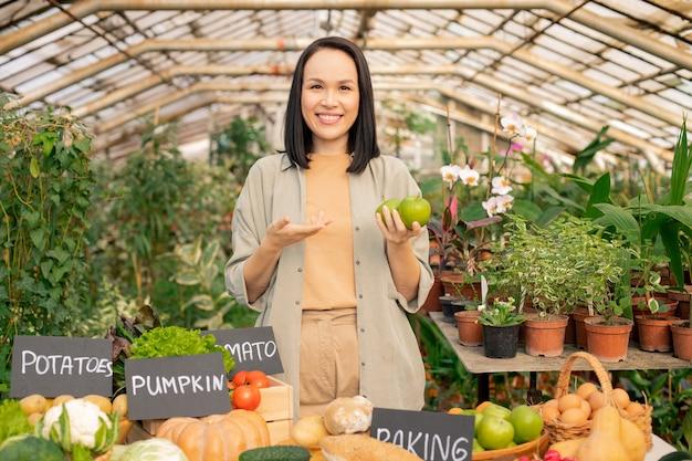 Porträt des lächelnden jungen asiatischen gärtners, der empfiehlt, äpfel zu essen, während bio-produkt auf bauernmarkt verkauft