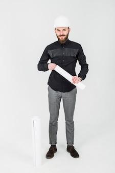 Porträt des lächelnden jungen ingenieurs, der den schützenden hardhat hält plan trägt