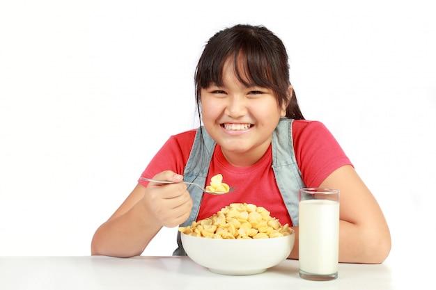 Porträt des lächelnden jungen mädchens, das frühstück gegen weiß hat