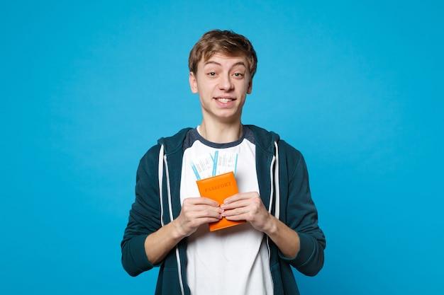 Porträt des lächelnden jungen mannes in freizeitkleidung halten reisepass, bordkarte einzeln auf blauer wandwand. menschen aufrichtige emotionen, lifestyle-konzept.