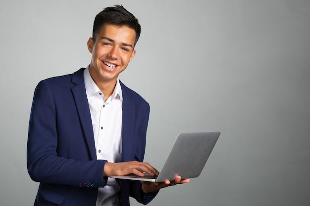 Porträt des lächelnden jungen mannes mit laptop