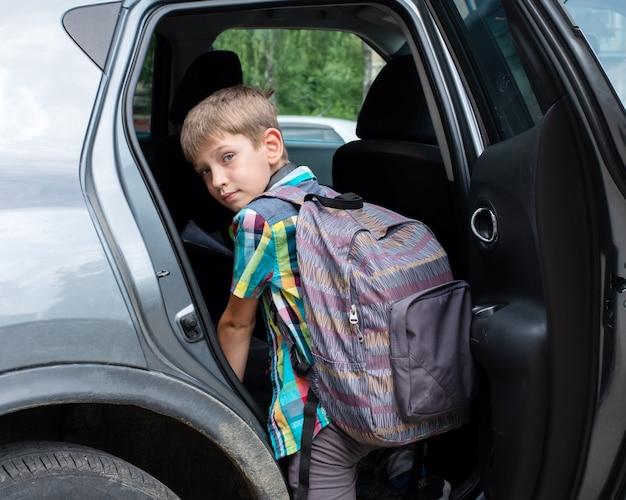 Porträt des lächelnden jungen mit schultasche, die in auto verliert. einen schüler nach der schule nehmen. der junge steigt ins auto.